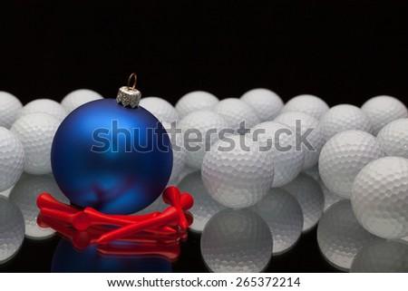 Blue Christmas decoration a golf balls on a black glass desk - stock photo