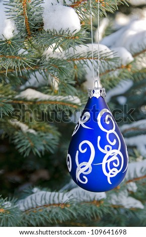 blue Christmas ornament hanging on snow covered blue spruce tree