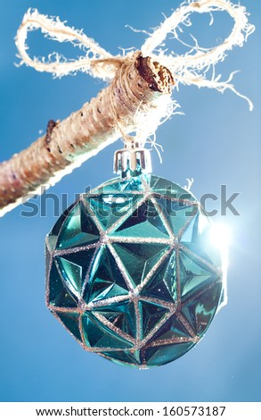 Blue Christmas ornament  highlighted with a bright light. Hanging from a birch tree branch.