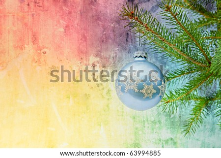 blue christmas ornament on christmas tree with rainbow grunge background