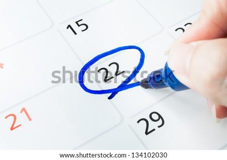 Blue circle. Mark on the calendar at 22. - stock photo