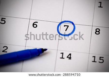 Blue circle. Mark on the calendar at 7. - stock photo