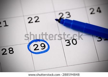 Blue circle. Mark on the calendar at 29. - stock photo