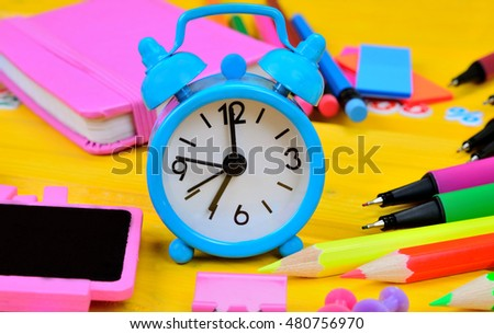 blue clock on yellow wooden table
