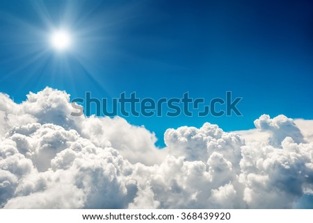 Blue clouds and sky and shining sun. Natural cloudscape background - stock photo