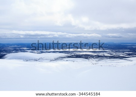 blue cloudy sky and arctic winter landscape from the mountain covered with snow above the Arctic Circle in Kirovsk Murmansk region Russia Khibiny - stock photo