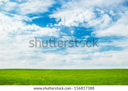 blue cloudy sky and green field of grass - stock photo
