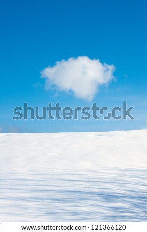 Blue cloudy sky and snow field in winter day