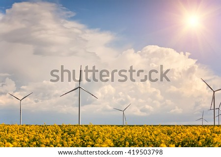 blue cloudy sky and windmills for electric power production on rural field of rape flowers. natural summer background
