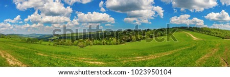 Blue cloudy sky over green hills and country road