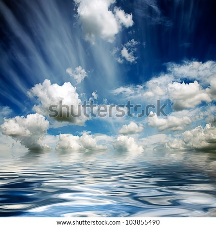 blue cloudy stormy sky reflected in water waves - stock photo