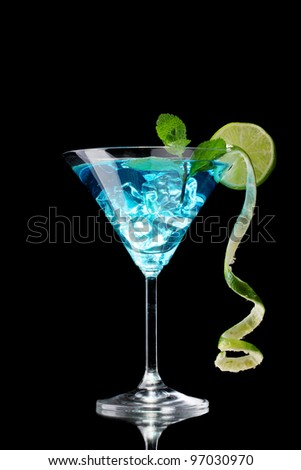 Blue cocktail in glass on black background - stock photo