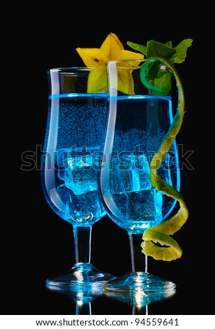 Blue cocktail in glasses on black background - stock photo