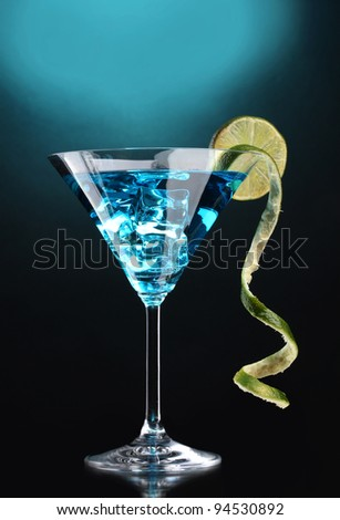 Blue cocktail in martini glass on blue background - stock photo