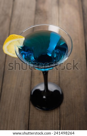 Blue cocktail in martini glass with slice of lemon - stock photo