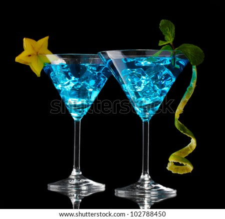 Blue cocktail in martini glasses on black background - stock photo