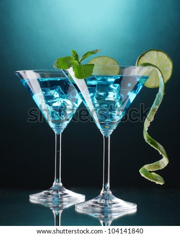 Blue cocktail in martini glasses on blue background - stock photo