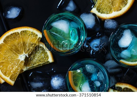 Blue cocktail with blue curacao liqueur and orange on a black background, top view, selective focus - stock photo