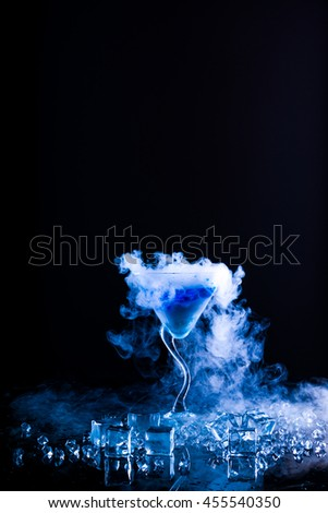 blue cocktail with dry ice vapor - stock photo