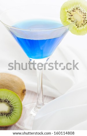 Blue cocktail with kiwi on wooden table