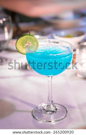 Blue cocktail with light from a candle