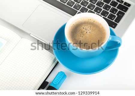 Blue coffee cup, laptop and office supplies. Closeup on white background