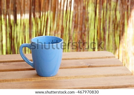 Blue coffee mug standing on wooden table