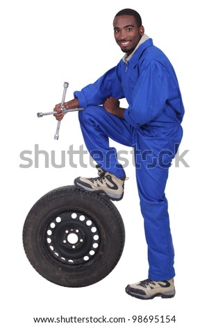 blue collar holding cross faucet with leg resting on pneumatic tyre - stock photo