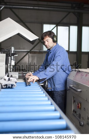 Blue collar worker at machine in factory