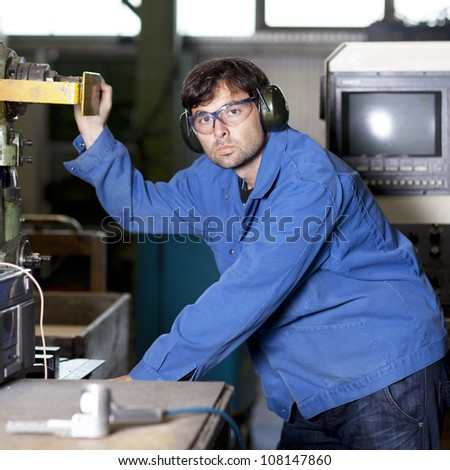 Blue collar worker at machine in factory - stock photo