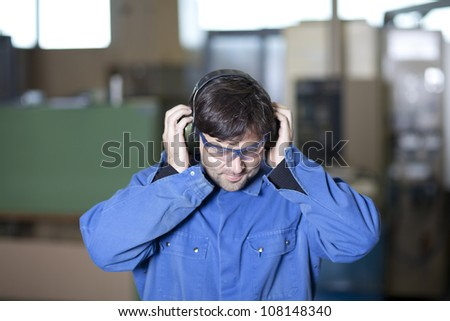 Blue collar worker at noisy workplace - stock photo