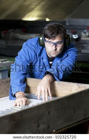 Blue collar worker in factory - stock photo