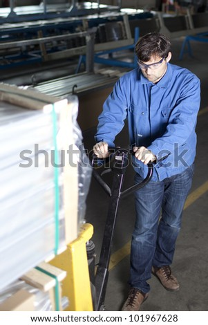 Blue-collar worker with pallet truck - stock photo