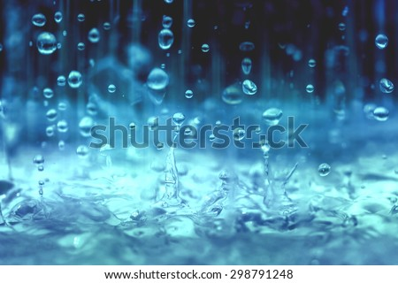 blue color tone of close up rain water drop falling to the floor  in rainy season  - stock photo