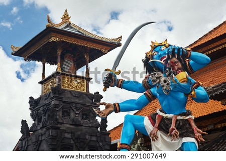 Blue colored traditional demon ogoh-ogoh holding a severed head before annual parade of horrible monsters - pengrupukan, which is held in the evening of Nyepi - Balinese New Year before day of silence