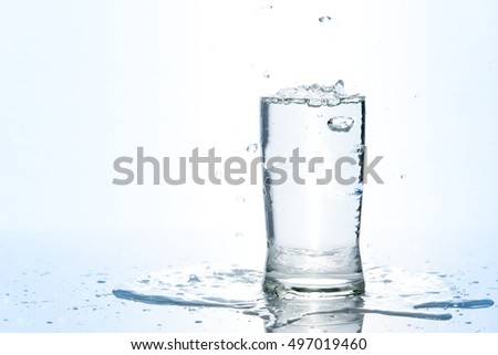 Blue colour tone of over pouring water in glass on white background