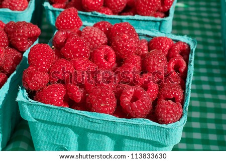 Blue container of a pile of Red Juicy Raspberries at the farmers market - stock photo