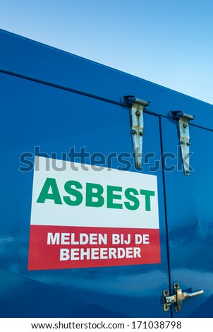 """Blue container with a warning sign containing the Dutch text """"Asbestos - Report to the Manager"""" for storage of the toxic asbestos material - stock photo"""