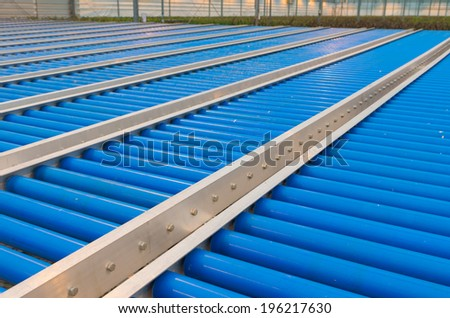 blue conveyor belt rollers in a greenhouse - stock photo