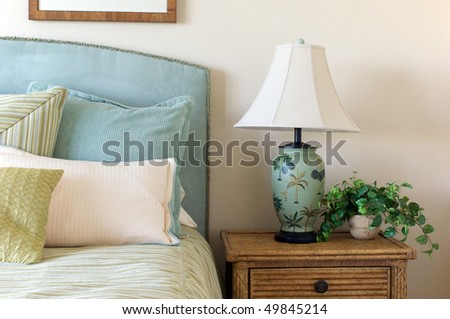 Blue corduroy headboard and pillows on bed with tropical looking lamp.