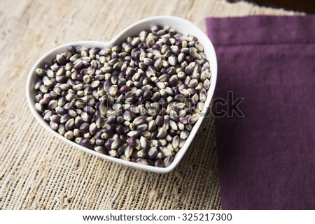 Blue corn popcorn in heart shaped bowl. - stock photo