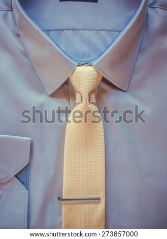 Blue cotton shirt and yellow tie with clip close up - stock photo