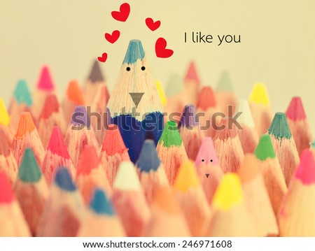 Blue crayon likes pink crayon on valentines day - stock photo