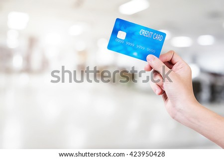 Blue credit card hold by hand to buy something over shopping mall background with copy space.
