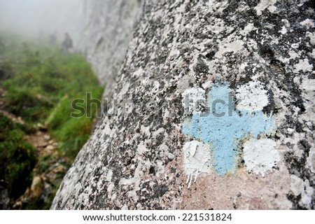 Blue cross symbol marking a tourist hiking route on the mountain - stock photo
