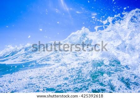 blue crystal water waves crashing on beach - stock photo