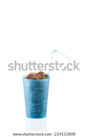 blue cup with straw full of coins , drink all your money or savings for vacation - stock photo