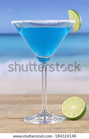 Blue Curacao cocktail on the beach while on vacation - stock photo