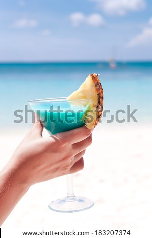 Blue Curacao cocktail with slice of pineapple on white beach in female hand - stock photo