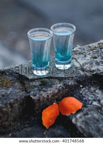 Blue Curacao liqueur with orange peel on a rock , selective focus - stock photo